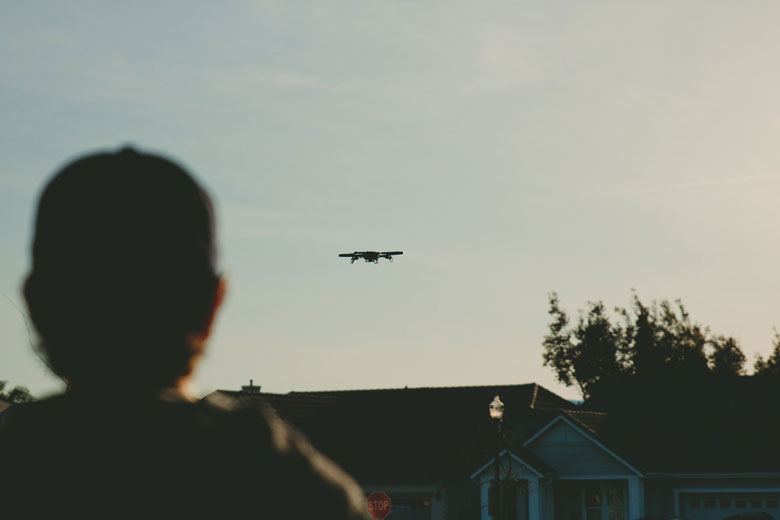 Man in baseball cap watching drone fly by at sunset in a neighborhood