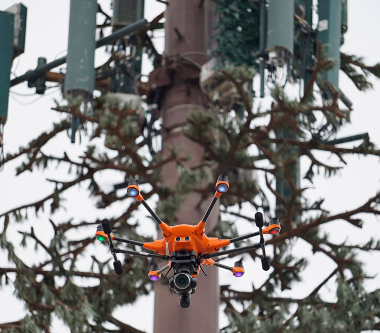 Camera-mounted drone for workplace inspection flying over a park