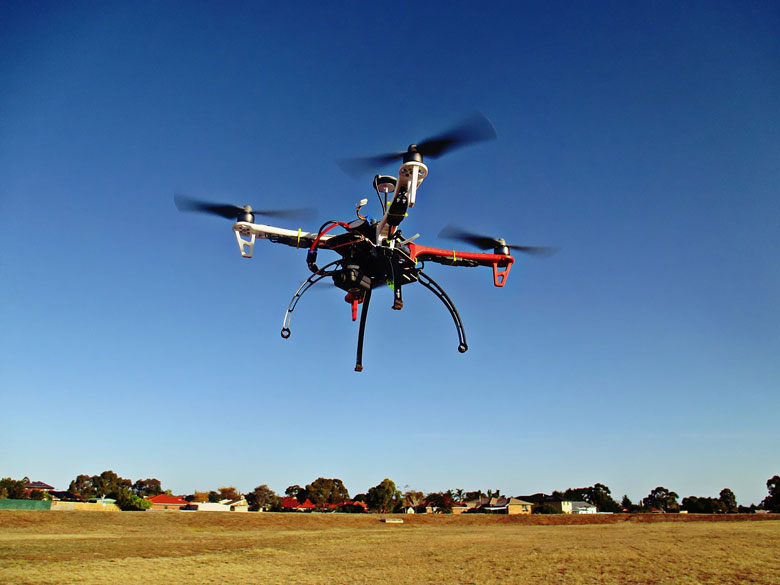 Remote control UAV drone with long range and wireless charging flying over field